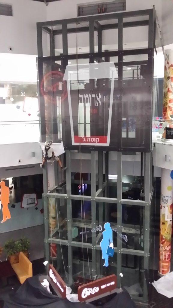 הדבקת מדבקת רשת על זכוכית במעלית בקניון מעלות